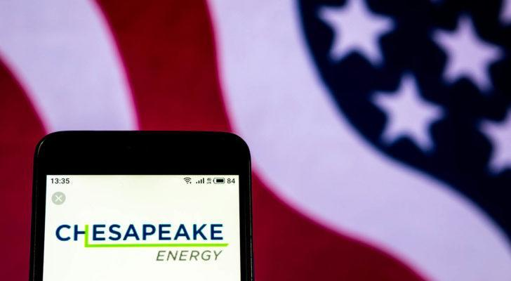 Chesapeake Energy (CHK) logo displayed on phone with American flag in background