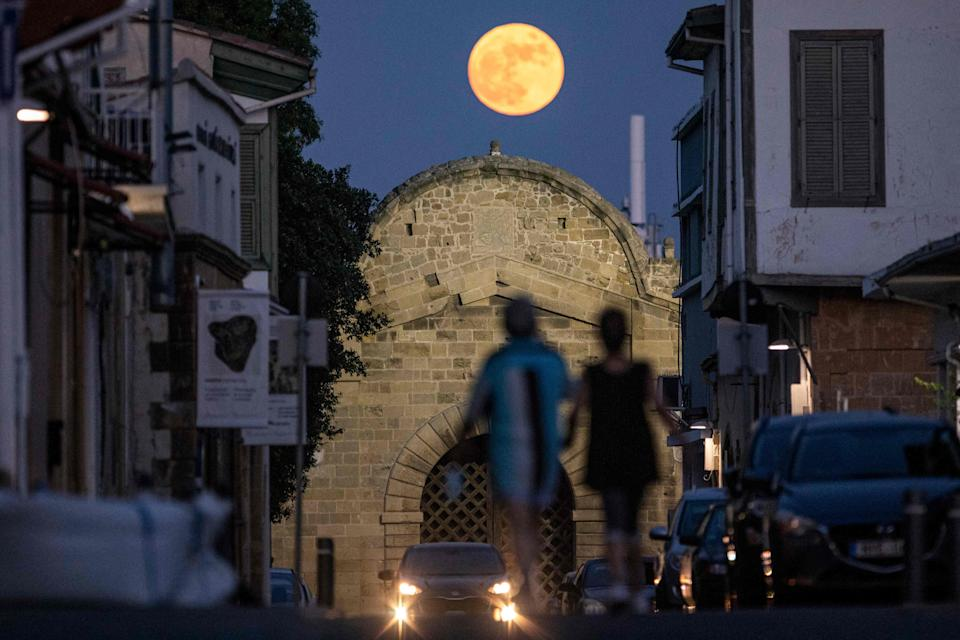 People walk beneath the rising Strawberry super moon towards the Venetian-built Famagusta gate in the old walled city of Cyprus' capital Nicosia on June 24, 2021.  Famagusta gate, one of the three main gates of the old city of Nicosia, was built in 1567 during the period of Venetian rule of the island of Cyprus. It was subsequently restored in 1821 during the reign of Ottoman Sultan Mahmud II, with the Sultan's seal (tugra) displayed atop its gatehouse.