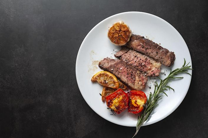 A steak sliced on a plate with roasted tomatoes, half a roasted garlic clove, and a sprig of rosemary garnish