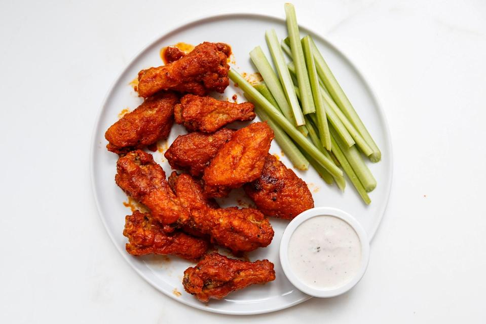 """Two key steps ensure extra-crisp wings: letting them sit at room temperature evens the cooking time, and the cornstarch dredge transforms into a crunchy shell when fried. If you like your wing sauce super spicy, increase the amount of cayenne. <a href=""""https://www.bonappetit.com/recipe/bas-best-buffalo-wings?mbid=synd_yahoo_rss"""" rel=""""nofollow noopener"""" target=""""_blank"""" data-ylk=""""slk:See recipe."""" class=""""link rapid-noclick-resp"""">See recipe.</a>"""