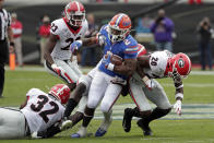 Florida running back Lamical Perine (2) is stopped after a short gain by the Georgia defense including linebacker Monty Rice (32) and defensive back J.R. Reed (20) during the first half of an NCAA college football game, Saturday, Nov. 2, 2019, in Jacksonville, Fla. (AP Photo/John Raoux)