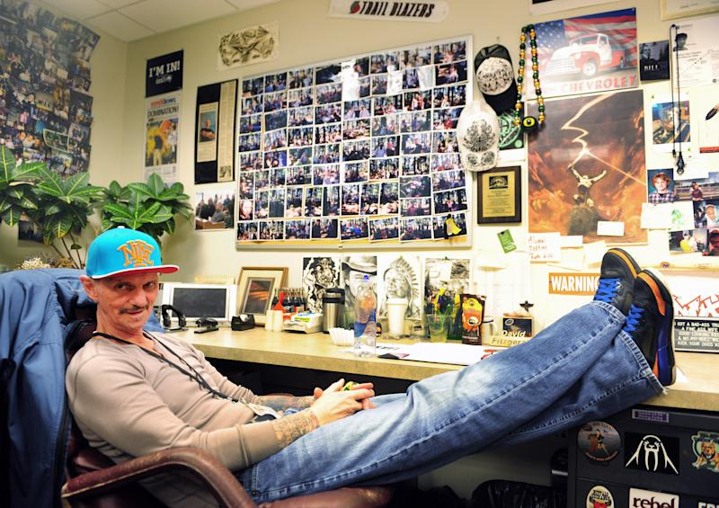 "In this Wednesday, March 12, 2014 photo, former heroin addict David Fitzgerald sits in his office in Portland, Ore. The photos on the wall include a collage from the previous year's group picnic. Recovering addicts smile and hold plates of food. Seven months later, Fitzgerald looks over the faces. Are they all still sober? Are they all still alive? ""Most of them,"" he says. ""Not all."" (AP Photo/Steve Dykes)"