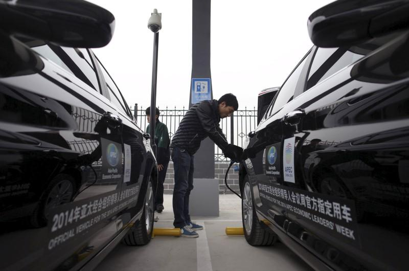 File photo of a man charging the batteries of BAIC Motors electric cars in Beijing