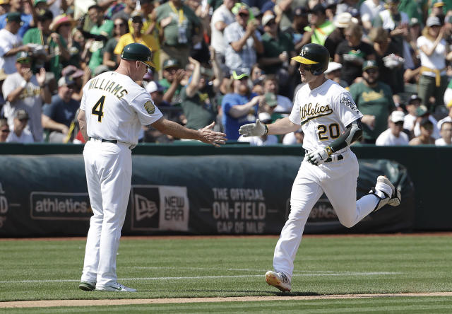 Oakland Athletics' Mark Canha, right, is congratulated by third base coach Matt Williams after hitting a solo home run against the New York Yankees during the fifth inning of a baseball game in Oakland, Calif., Monday, Sept. 3, 2018. (AP Photo/Jeff Chiu)