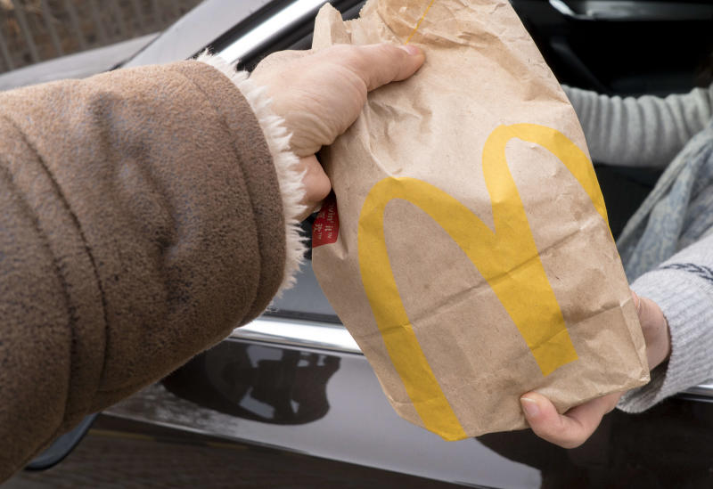 A person receives a bag of McDonald's in their car.