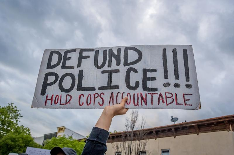 """A participant holding a """"Defund Police"""" sign at a protest. Hundreds of protesters flooded the streets of Crown Heights in Brooklyn, New York, to demand the defunding of the police force and to demonstrate against police brutality in the wake of George Floyd's death. (Photo: Erik McGregor via Getty Images)"""