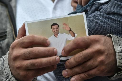 "A supporter holds a picture of Demirtas, Turkey's leading Kurdish politician, who urged supporters to campaign in his name as ""my voice and my breath"""