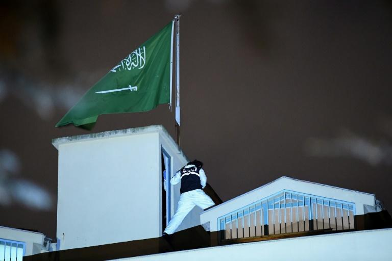 A Turkish forensic expert stands next to the Saudi flag on the roof of the consulate in Istanbul on October 15, 2018 during a much anticipated eight-hour search in the investigation into missing Saudi journalist Jamal Khashoggi