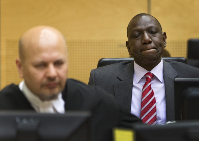 Kenya's Deputy President William Ruto, right, awaits the start of his trial in the courtroom of the International Criminal Court (ICC) in The Hague, Netherlands, Tuesday, Sept. 10, 2013. At left defense counsel Karim Khan. The trial of Kenya's deputy president has opened at the ICC on charges of orchestrating deadly violence in the aftermath of his country's disputed 2007 election. Ruto and broadcaster Joshua Sang are both accused of murder, deportation and persecution. They insist they are innocent. (AP Photo//Michael Kooren, Pool)