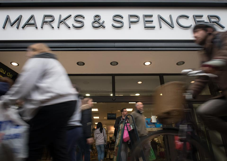 Shoppers pass a branch of Marks and Spencer on the main shopping street. (Photo by Matt Cardy/Getty Images)