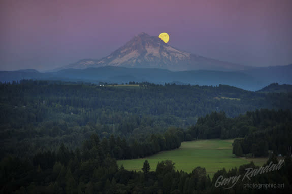 The blue moon shines behind Mount Hood, Oregon, in this photo by Gary Randall.