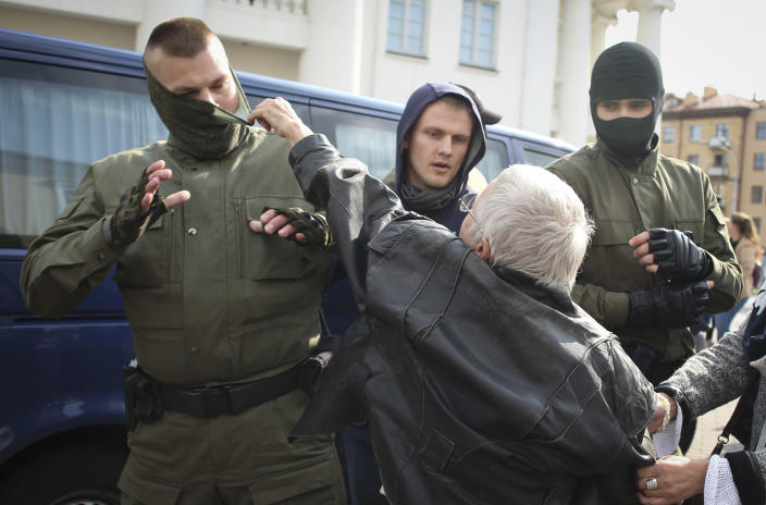 An elderly woman rips the mask off a police officer during an opposition rally to protest the official presidential election results in Minsk, Belarus, Saturday, Sept. 12, 2020. (Tut.by via AP)