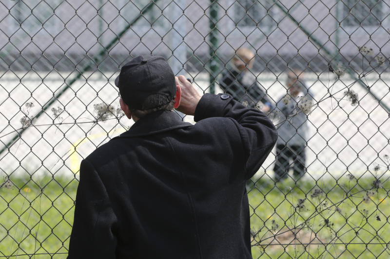 Hajdar Selimovic calls to his nephew Ismail behind a fence at a detention center where authorities have brought back from Syria 110 Kosovar citizens, mostly women and children in the village of Vranidol on Sunday, April 20, 2019. Four suspected fighters have been arrested, but other returnees will be cared for, before being sent to homes over the coming days, according to Justice Minister Abelard Tahiri.(AP Photo/Visar Kryeziu)