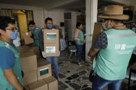 City workers carry medical and food supply kits being taken for home delivery to households with a member suffering from symptoms of COVID-19, in the Coyoacan district of Mexico City, Thursday, April 9, 2020. To help halt the spread of the new coronavirus, the Mexican megalopolis is making home deliveries to households with a symptomatic person, providing kits containing food staples, face masks, gloves, antibacterial gel, paracetamol, a thermometer, and benefits cards with a balance of 1000 pesos (around $42). (AP Photo/Rebecca Blackwell)
