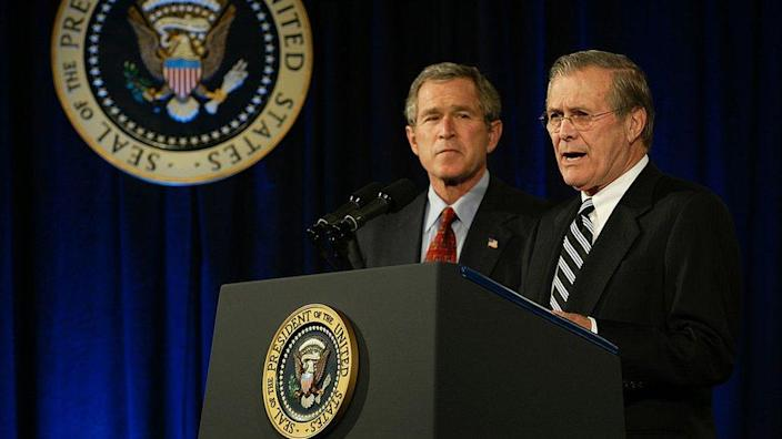 Rumsfeld and George Bush at podium with presidential seal, in 2002 image