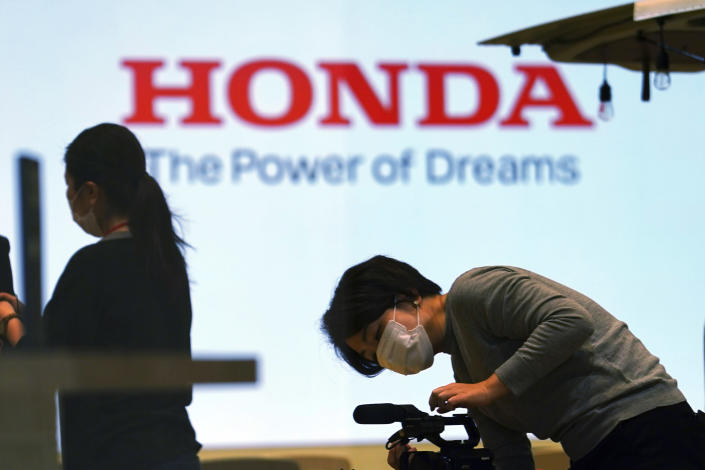 A woman wearing a protective mask to help curb the spread of the coronavirus works near the logo of Honda Motor Company at a showroom Thursday, May 13, 2021, in Tokyo. Honda swung into the black in January-March, recording a 213 billion yen ($2 billion) profit, despite the ongoing uncertainties unleashed by the coronavirus pandemic, the results, released Friday, May 14, 2021. (AP Photo/Eugene Hoshiko)