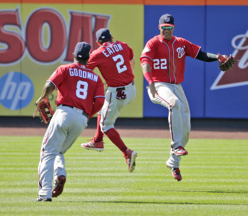 Washington Nationals outfielders Juan Soto, right, Adam Eaton, center, and Brian Goodwin celebrate after the baseball game against the New York Mets at Citi Field, Sunday, July 15, 2018, in New York. The Nationals defeated the Mets 6-1. (AP Photo/Seth Wenig)