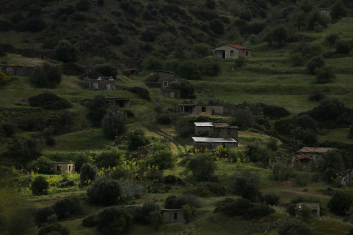 The abandoned village of Varisia is seen inside the U.N controlled buffer zone that divide the Greek, south, and the Turkish, north, Cypriot areas since the 1974 Turkish invasion, Cyprus, on Friday, March 26, 2021. Cyprus' endangered Mouflon sheep is one of many rare plant and animal species that have flourished a inside U.N. buffer zone that cuts across the ethnically cleaved Mediterranean island nation. Devoid of humans since a 1974 war that spawned the country's division, this no-man's land has become an unofficial wildlife reserve. (AP Photo/Petros Karadjias)