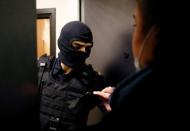 Lawyer Svetlana Davydova shows her identification to a law enforcement officer standing outside an apartment of Russian opposition leader Alexei Navalny in Moscow