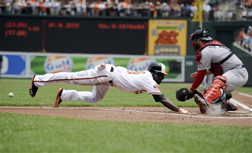 Baltimore Orioles' Xavier Avery, left, slides home to score a run against Boston Red Sox catcher Kelly Shoppach, right, on a sacrifice fly by Chris Davis during the first inning of a baseball game, Wednesday, May 23, 2012, in Baltimore. (AP Photo/Nick Wass)