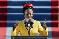Amanda Gorman, in a yellow coat, reads a poem at the inauguration.