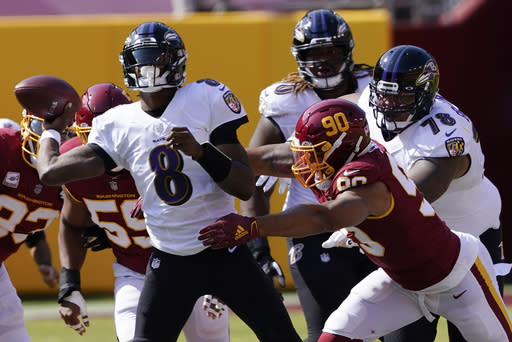 Baltimore Ravens quarterback Lamar Jackson (8) works against Washington Football Team defensive end Montez Sweat (90) during the first half of an NFL football game, Sunday, Oct. 4, 2020, in Landover, Md. (AP Photo/Susan Walsh)