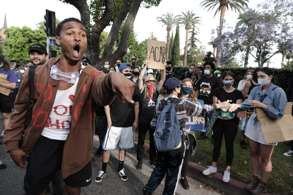 """A """"Black Lives Matter"""" protesters screams at a line of police during a protest outside Los Angeles Mayor Eric Garcetti's house."""