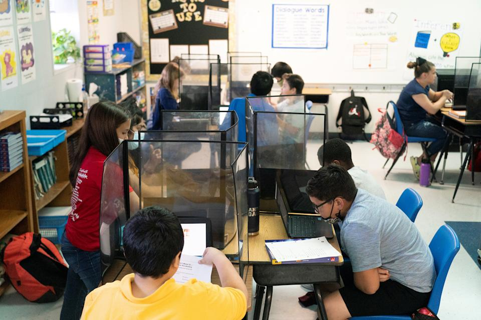 5th graders at Louise Elementary School study in a classroom with plastic partitions, during the coronavirus disease (COVID-19) pandemic in Louise, Texas, U.S., November 20, 2020. Picture taken November 20, 2020. REUTERS/Go Nakamura