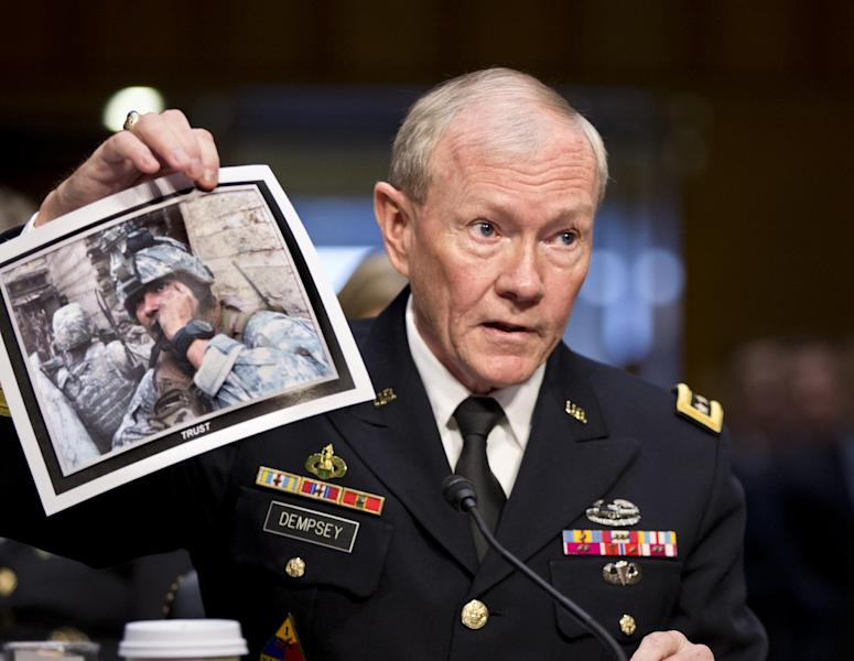 Gen. Martin Dempsey, chairman of the Joint Chiefs of Staff, holds up a photo of a deployed American soldier as he testifies before the Senate Armed Services Committee at his reappointment hearing, on Capitol Hill in Washington, Thursday, July 18, 2013. Dempsey said during congressional testimony Thursday that he has provided President Obama with options for the use of force in Syria. (AP Photo/J. Scott Applewhite)