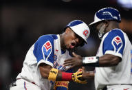 Atlanta Braves' Ronald Acuna Jr., left, is congratulated by first base coach Eric Young Sr. after Acuna's home run during the seventh inning of a baseball game against the Miami Marlins on Wednesday, April 14, 2021, in Atlanta. (AP Photo/Brynn Anderson)