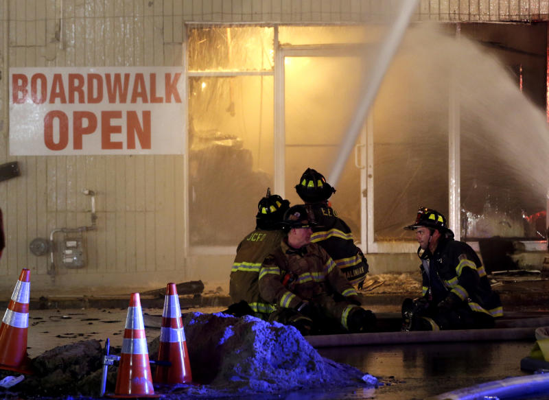 Firefighters sit on a hose while battling a blaze in a building on the Seaside Park boardwalk on Thursday, Sept. 12, 2013, in Seaside Park, N.J. The fire began in a frozen custard stand on the Seaside Park section of the boardwalk and quickly spread north into neighboring Seaside Heights. (AP Photo/Julio Cortez)