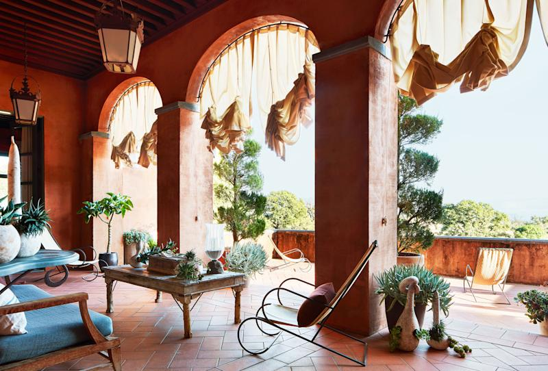 Balloon shades in a Delany & Long fabric hang from loggia arches at a residence in Northern California. Iron deck chairs by The Heveningham Collection.