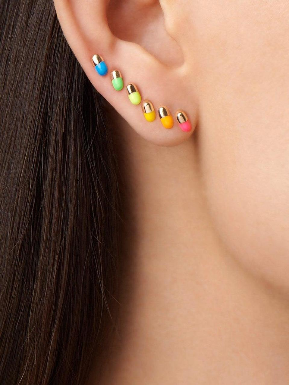 """<h3>Alison Lou Tiny Pill Single Earring<br></h3> <br>Alison Lou is known to work magic with enamel to create cheeky emoji jewelry, so this assortment of gilded multi-colored pill earrings are a natural next step.<br><br><em>Shop <strong><a href=""""https://www.ylang23.com/"""" rel=""""nofollow noopener"""" target=""""_blank"""" data-ylk=""""slk:Ylang23"""" class=""""link rapid-noclick-resp"""">Ylang23</a></strong></em><br><br><strong>Alison Lou</strong> Glitter Tiny Pill Stud Single Earring, $, available at <a href=""""https://go.skimresources.com/?id=30283X879131&url=https%3A%2F%2Fwww.ylang23.com%2Falison-lou-silver-glitter-tiny-pill-stud-single-earring-yellow-gold%2Fp%2FAL-36031228"""" rel=""""nofollow noopener"""" target=""""_blank"""" data-ylk=""""slk:Ylang23"""" class=""""link rapid-noclick-resp"""">Ylang23</a><br><br><br>"""