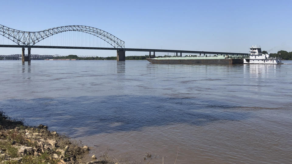 A boat hauling barges down the Mississippi River moves toward the Interstate 40 bridge linking Tennessee and Arkansas on Friday, May 14, 2021, in Memphis, Tenn. The U.S. Coast Guard reopened a section of the river near Memphis on Friday, three days after river traffic was shut down when a crack was found in the bridge. (AP Photo/Adrian Sainz)