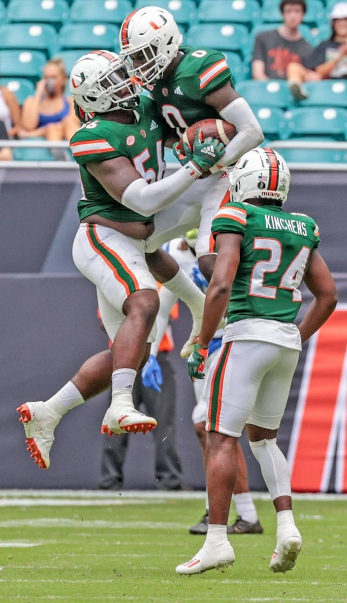 Miami Hurricanes safety James Williams (0) and Miami Hurricanes defensive lineman Leonard Taylor (56) celebrate after Williams intercepts the ball in the fourth quarter during game against Central Connecticut State Blue Devils at Hard Rock Stadium in Miami Gardens on Saturday, September 25, 2021.
