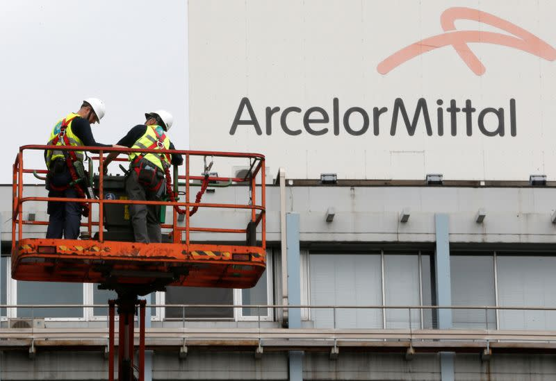 Workers stand near the logo of ArcelorMittal at the steel plant in Ghent