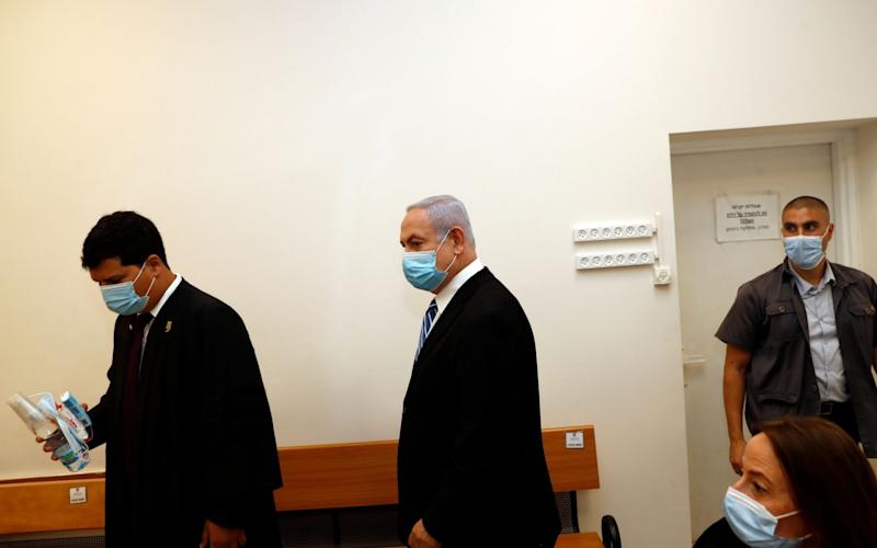 Israeli Prime Minister Benjamin Netanyahu (C) wearing a face mask, stands inside the court room on the first day of his trial for alleged corruption crimes - RONEN ZVULUN/POOL/EPA-EFE/Shutterstock/Shutterstock