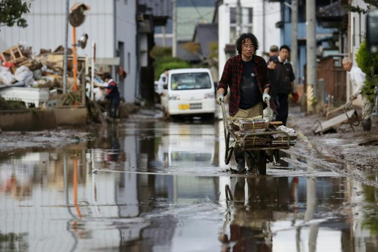 A man removes muddy items at a flood-affected area in Nagano -- Japan's government pledged financial support to affected regions without specifying how much aid it would set aside