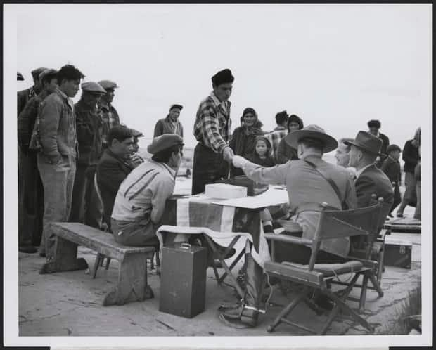 A Dene man accepts money from a fully uniformed Mountie seated behind a table draped with a British flag in Yellowknife. Food and money were distributed in communities after — and sometimes before — Treaty 11 was signed. (Library and Archives Canada - image credit)