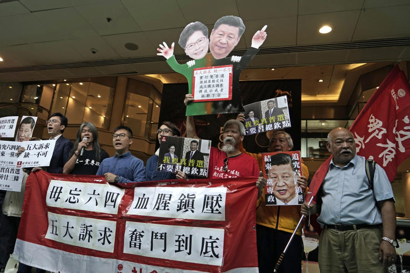 "Pro-democracy activists hold up placards of Chinese President Xi Jinping and Hong Kong Chief Executive Carrie Lam, at a ferry terminal in Hong Kong, Wednesday, Dec. 18, 2019. A ferry company barred a Hong Kong activist ""Long Hair"", whose real name is Leung Kwok-hung, from boarding a boat Wednesday to Macao, where Chinese President Xi Jinping is slated to arrive for the 20th anniversary of Macau's return to China, The placards read ""Five demands, not one less"", ""I want genuine universal suffrage"", ""Vindicate June 4th"" and ""Put an end to one-party Dictatorship"". (AP Photo/Kin Cheung)"