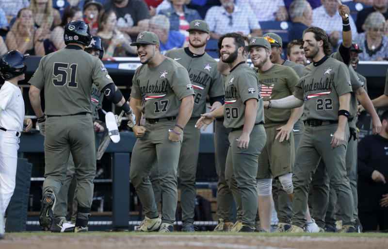 Vanderbilt right fielder JJ Bleday (51) is congratulated by teammates after hitting a home run against Michigan during sixth the inning in Game 1 of the NCAA College World Series baseball finals in Omaha, Neb., Monday, June 24, 2019. (AP Photo/Nati Harnik)