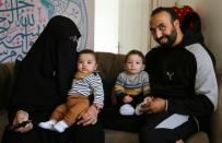 Mohamed Abdallah, his wife Merna Reda and their biological son Soliman, sit next to Dawood, an orphan they sponsor, in their home in Cairo