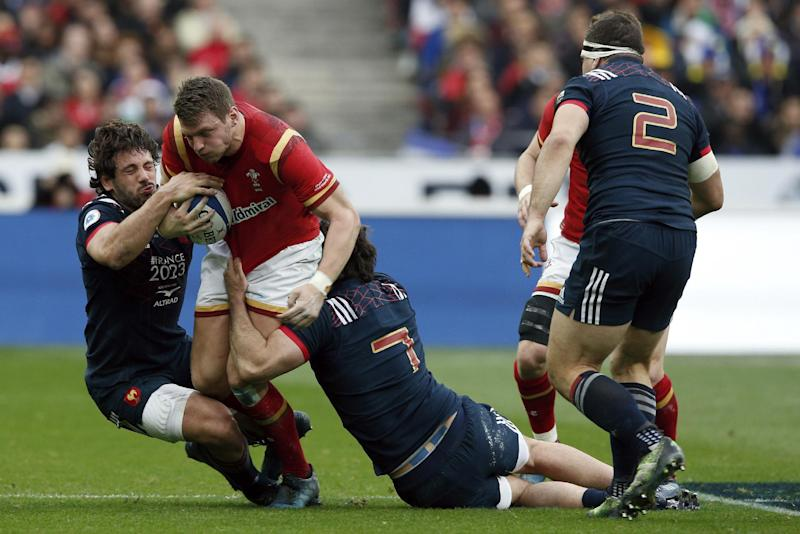Wales' Scott Williams is tackled by France's Remi Lamerat, left, and Kevin Gourdon during a Six Nations rugby union international match between France and Wales at the Stade de France stadium, in Saint Denis, north of Paris, Saturday, March 18, 2017. (AP Photo/Thibault Camus)