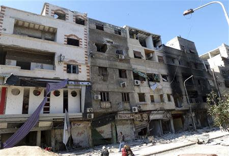Civilians walk past damaged building at the Palestinian refugee camp of Yarmouk, south of Damascus, February 12, 2014. Picture taken February 12, 2014. REUTERS/Mohamad Mohamad