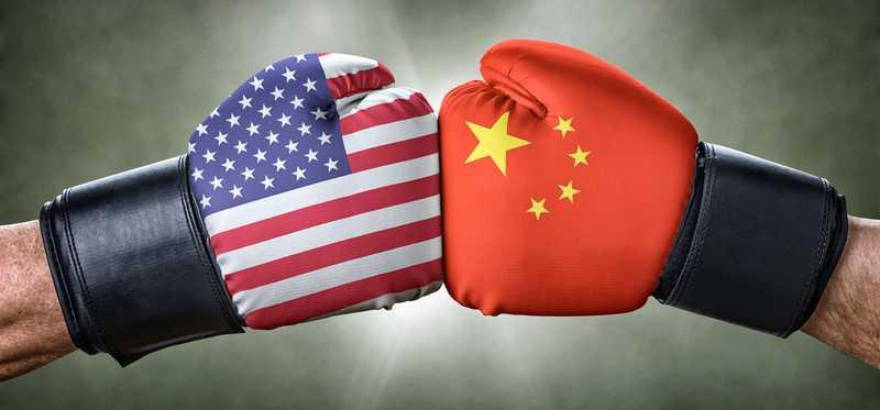 Boxing gloves touching with U.S. and China flag graphics.