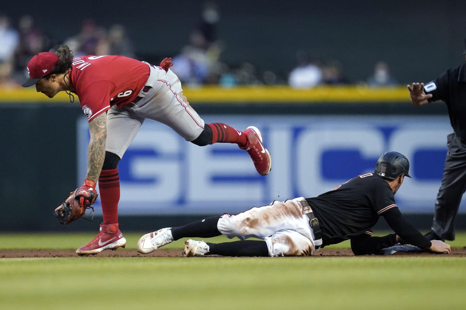 Cincinnati Reds second baseman Jonathan India (6) is unable to step on second base as Arizona Diamondbacks' Tim Locastro, right, slides safely into the bag on a single hit by Christian Walker during the fifth inning of a baseball game Saturday, April 10, 2021, in Phoenix. (AP Photo/Ross D. Franklin)