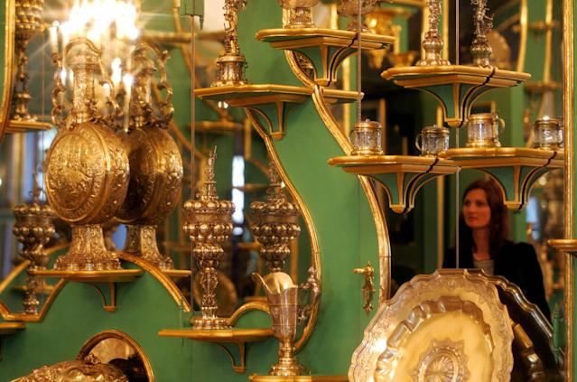 A visitor looks at precious exhibits of the Green Vault at Dresden's Royal Palace. The Green Vault, named for the pale green hue of its domed ceiling, was founded in 1723 by August II, the prince-elector of Saxony and king of Poland. Photo: Norbert Millauer/DDP/AFP via Getty