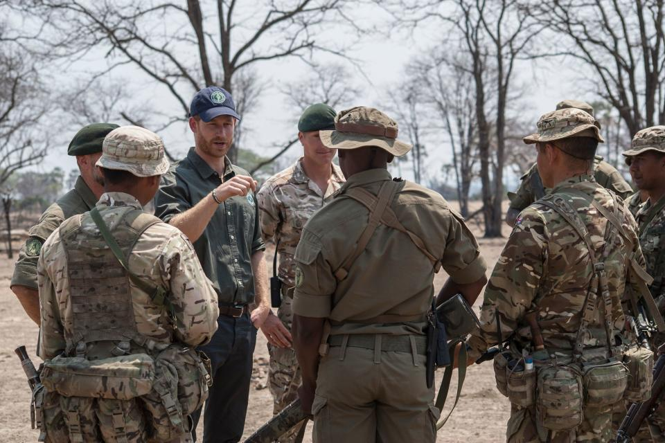 TOPSHOT - Duke of Sussex Prince Harry (L) talks with British Soldiers and Malawian game rangers of Liwonde national park after he observed demonstrations on how to fight poaching following a memorial service at the place where British guardsman Matthew Talbot, 22, of the Coldstream Guards, was killed in C-IWT Operation a few months ago, at Liwonde National park on September 30, 2019. - Gdsm Talbot was killed by an elephant who charged at him. (Photo by Amos GUMULIRA / AFP) (Photo by AMOS GUMULIRA/AFP via Getty Images)