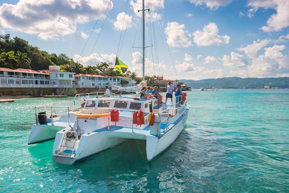 People enjoy a catamaran boat tour at Doctor's Cave Beach in Montego Bay Jamaica on a cloudy day. (Getty Images)