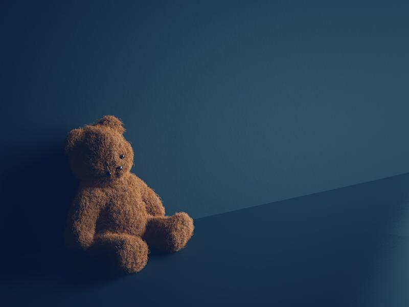 Teddy bear with torn eye sits in dark room. Child abuse and violence concept.